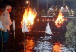 夏越祓 茅の輪くぐり 人形流し : 篝火に照らし出され人形が投じられる